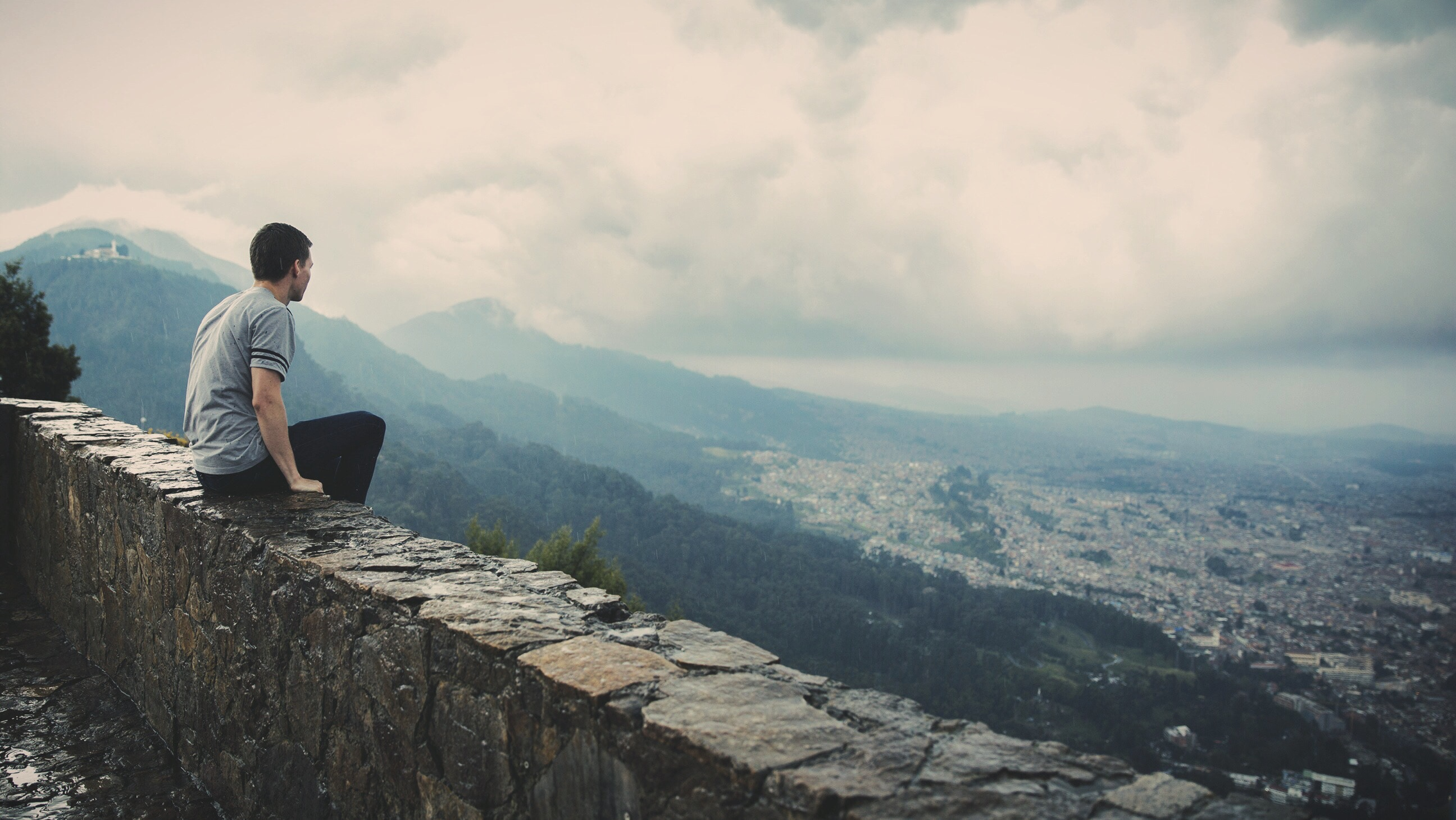 Man sitting on a wall overlooking a city