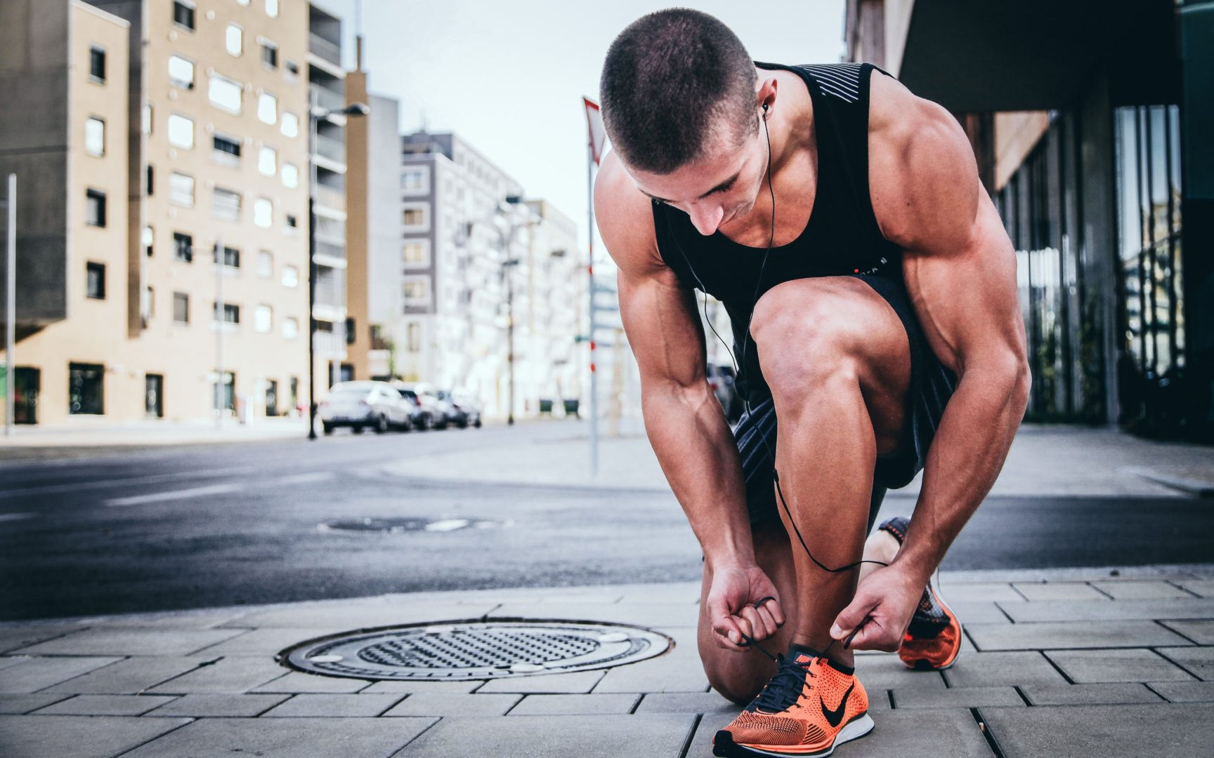 Man in the street tying shoes on way to gym