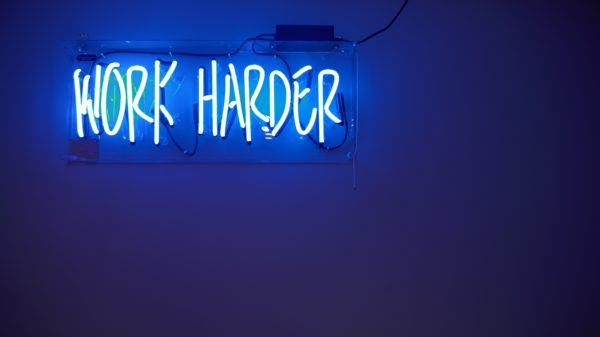 "Neon sign reading ""work harder"""